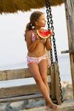 Sommerfreude, reizendes Mädchen, das frische Wassermelone auf dem Strand isst Stockbild
