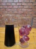 Sommergetränk, alkoholfreies Getränk der frischen Trauben und Eistraubenballwürfel im Glasglas mit Unschärfeziegelstein blockiere Stockfoto