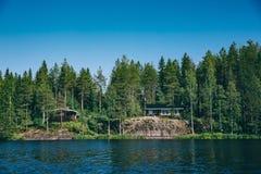 Sommerhäuschen oder -Blockhaus durch den blauen See in ländlichem Finnland Stockfotografie