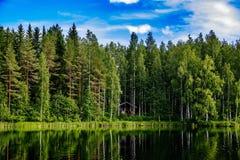 Sommerhäuschen oder -Blockhaus durch den blauen See in ländlichem Finnland Lizenzfreies Stockbild