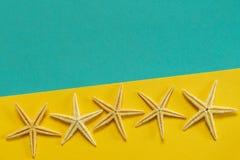 Sommerhintergrund des gelben und blauen Papiers mit Starfish, Symbol Lizenzfreie Stockfotos