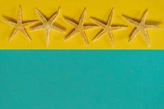Sommerhintergrund des gelben und blauen Papiers mit Starfish, Symbol Stockfotos