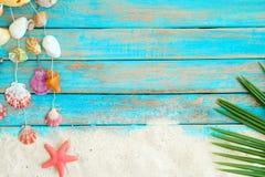Sommerhintergrund mit dem Strandsand, starfishs Kokosnussblättern und Oberteildekoration, die am blauen hölzernen Hintergrund hän