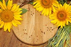 Sommerhintergrund mit Sonnenblumen auf hölzernem Brett Lizenzfreie Stockfotografie
