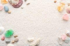 Sommerhintergrund von Muscheln und von Seekieseln auf Strandsand Lizenzfreie Stockbilder