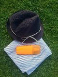 Sommerhut, Badetuch und Lichtschutzlotion auf dem Gras Stockfotos