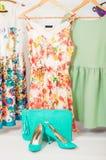 Sommerkleider, die an den Aufhängern und an den Schuhen hängen stockfotos