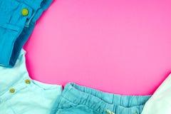 Sommerkleidung, -kurze Hosen, -hosen und -t-Shirts auf einem rosa Hintergrund stockfotos
