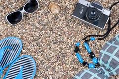 Sommerkleidung und -sachen für Feiertage auf dem Strand Stockbild