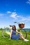 Sommerkonzept - Frau, die auf dem Gras mit Weinlesefahrrad sitzt Stockfoto