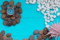 Sommerkonzept: Muscheln und Kiesel mit Wecker auf Holz b Lizenzfreies Stockfoto