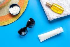 Sommerkosmetik mit Draufsicht des blauen Hintergrundes der Schutzcreme und -hutes Stockfoto