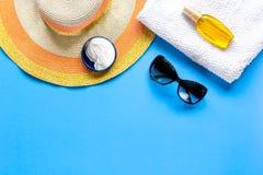 Sommerkosmetik mit Draufsichtspott des Hintergrundes der Schutzcreme und -hutes blauem oben Lizenzfreies Stockbild