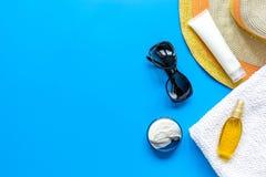Sommerkosmetik mit Draufsichtspott des Hintergrundes der Schutzcreme und -hutes blauem oben Lizenzfreie Stockbilder