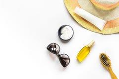 Sommerkosmetik mit Draufsichtspott des Hintergrundes der Schutzcreme und -hutes weißem oben Lizenzfreie Stockfotos