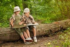 Sommerlager, kampierende Pfadfinderkinder und gelesene Karte im Wald lizenzfreie stockfotos