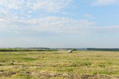 Sommerlandschaft auf dem Gebiet Das Auto geht weit auf dem Gebiet Blauer Himmel in den Wolken Stockfotos