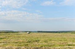 Sommerlandschaft auf dem Gebiet Das Auto geht weit auf dem Gebiet Blauer Himmel in den Wolken Lizenzfreie Stockfotos