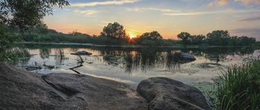 Sommerlandschaft auf den Banken des Flusses bei Sonnenuntergang stockfoto