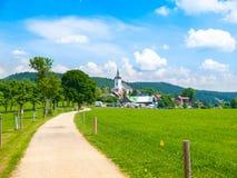 Sommerlandschaft mit üppiger grüner Wiese, Landstraße und weißer ländlicher Kirche Prichovice, Nord-Böhmen, tschechisch Lizenzfreies Stockfoto