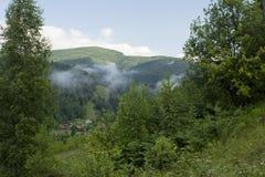Sommerlandschaft mit dem Dorf in einem Gebirgstal Stockfotografie