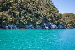 Sommerlandschaft mit den Leuten, die in einem gelben Kajak im klaren Ozean Kayak fahren lizenzfreies stockfoto