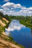 Sommerlandschaft mit Fluss und blauem Himmel Stockbilder