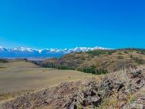 Sommerlandschaft mit Schnee bedeckte Berge auf dem Horizont mit einer Kappe Stockfoto