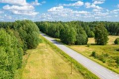 Sommerlandschaft mit Straße unter der Walddraufsicht Stockfotos