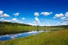 Sommerlandschaft mit Wiesen, Wald, Fluss, blauem Himmel und Reflexion von weißen Wolken Stockbild