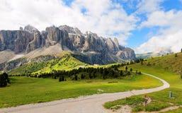 Sommerlandschaft von majestätischen Bergen u. Wanderwegen Sella, die im grünen grasartigen Tal an einem bewölkten sonnigen Tag stockfotos
