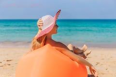 Sommerlebensstilporträt des hübschen Mädchens sitzend auf dem orange aufblasbaren Sofa auf dem Strand von Tropeninsel Entspannung stockfotos