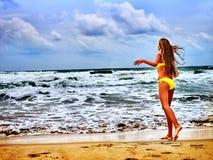Sommermädchenmeer im gelben Badeanzug Stockfoto