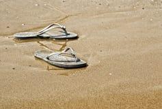 Sommermädchenschuhe auf dem Strand Stockfotos