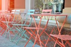 Sommermöbel machten vom Metall nahe Café Blaue und korallenrote Metalltabellen und -stühle am sonnigen Tag lizenzfreies stockbild