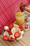 Sommermittagessen: schneiden Sie Bananen, Erdbeeren und Saft Stockfotografie