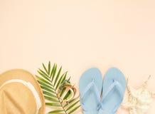 Sommermode, Sommerausstattung auf Sahnehintergrund Blaue Flipflops, Muschel, hölzernes Armband und Strohhut Flache Lage, Spitze lizenzfreie stockfotografie