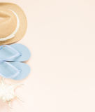 Sommermode, Sommerausstattung auf Sahnehintergrund Blaue Flipflops, Muschel und Strohhut Flache Lage, Draufsicht lizenzfreie stockbilder