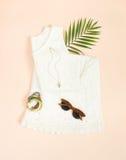 Sommermode, Sommerausstattung auf Sahnehintergrund Weißes Spitzekleid, Retro- Sonnenbrille, hölzernes Armband Flache Lage, Draufs stockbild