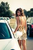Sommermodemädchen im goldenen Kleid stockfotografie
