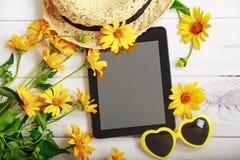 Sommermuster mit gelben Gänseblümchen, Strohhut, Tablette und glasse Lizenzfreie Stockfotos