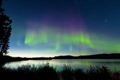 Sommernachtnordlichter über See Laberge lizenzfreie stockfotos