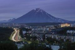 Sommernachtstadtbild, das Automobile auf Stadtstraße auf Hintergrund des Vulkans fährt lizenzfreie stockbilder
