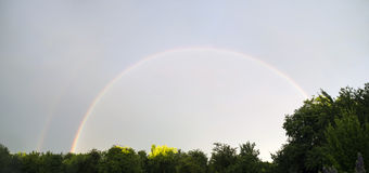 Sommerpanorama des Regenbogens nach dem Regen Stockfotos