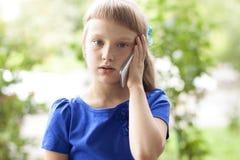 Sommerpark des kleinen Mädchens, der am Telefon, in einem blauen Kleid spricht Blond Stockfotografie