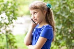 Sommerpark des kleinen Mädchens, der am Telefon, in einem blauen Kleid spricht Blond Lizenzfreie Stockfotos