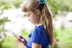 Sommerpark des kleinen Mädchens, der am Telefon, in einem blauen Kleid spricht Blond Lizenzfreie Stockfotografie