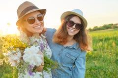 Sommerporträt der glücklichen Mutter und der Tochter auf der Natur in der Wiese, goldene Stunde stockfoto