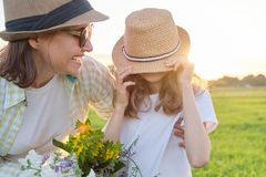 Sommerporträt der glücklichen Mutter und der Tochter auf der Natur in der Wiese, goldene Stunde lizenzfreies stockfoto