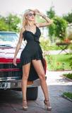 Sommerporträt der stilvollen blonden Weinlesefrau mit den langen Beinen, die nahe rotem Retro- Auto aufwerfen moderne attraktive  Lizenzfreie Stockfotos